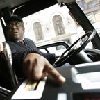 New York City bus driver David Smith points out how to use the fare system to a passenger.