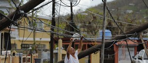 A resident uses a plastic bag to move downed power cables in Puerto Rico.