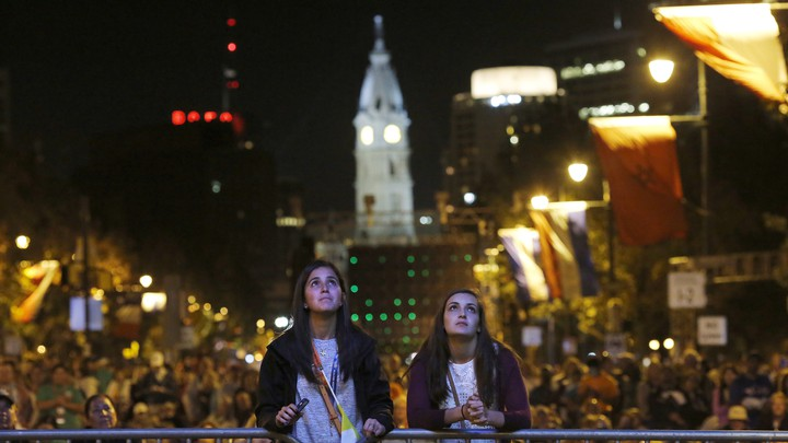 Two teens look at a television screen during Pope Francis's 2015 visit to Philadelphia.