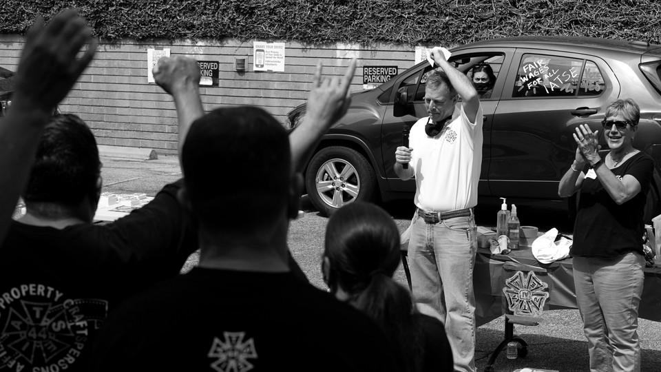Black and white photo of Mike Miller, vice president of the International Alliance of Theatrical Stage Employees, speaking to members at a rally