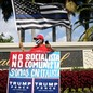 """A man in a MAGA hat stands with a sign that reads """"Not socialist, not communist, we are capitalist"""" in Spanish"""