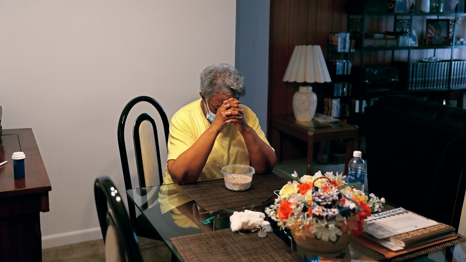 A woman sits at a table in her apartment, praying