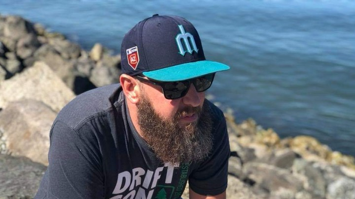 A bearded man in a baseball cap sits on some rocks by the water.
