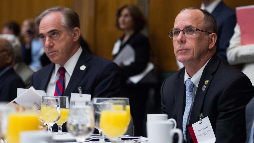 Veterans Affairs Secretary David Shulkin and award winner Rory Cooper sit at a table at the 2017 Sammies finalist-announcement breakfast.
