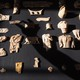A technician at the British Museum casts a shadow over carved ivory artifacts from Nimrud, Iraq.