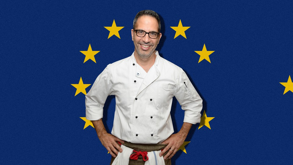 Yotam Ottolenghi stands in front of a European Union flag.