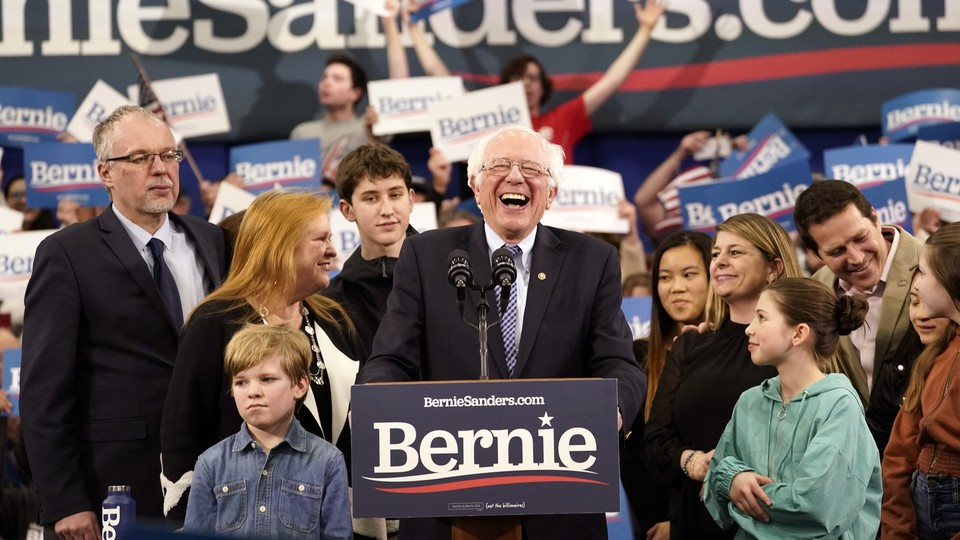 Bernie Sanders, standing at a lectern, surrounded by his family, laughs as he looks onto a crowd.