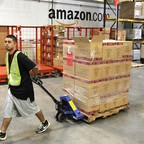 An Amazon worker in Phoenix, Arizona, wheels a dolly with boxes.