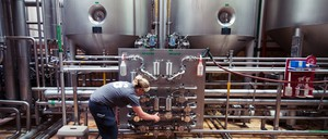 A woman adjusts the equipment in front of large metal vats at a brewery.