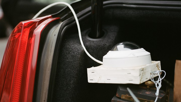 A white surveillance camera in the trunk of a car