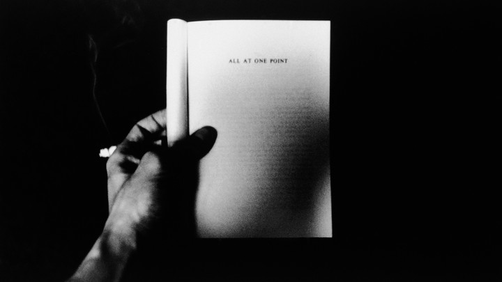 a hand holding open a book