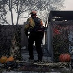 photo: A firefighter works to clear a house destroyed by a wildfire in Los Angeles.