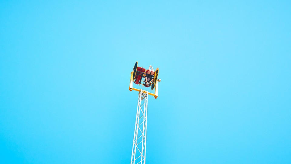 A person sits upside down on an amusement park ride, high in the air.