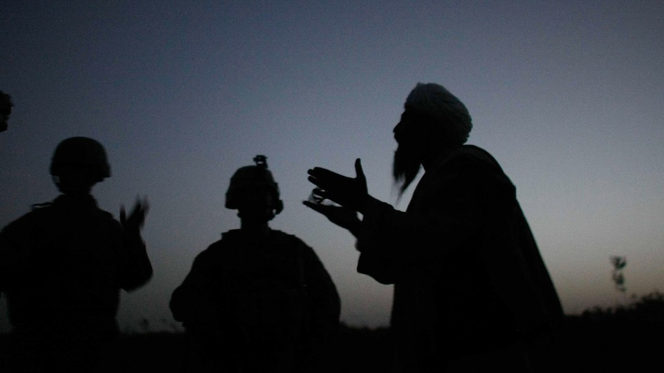 Silhouettes of three people, two who appear to have soldier helmets on and one with what looks like a head wrap