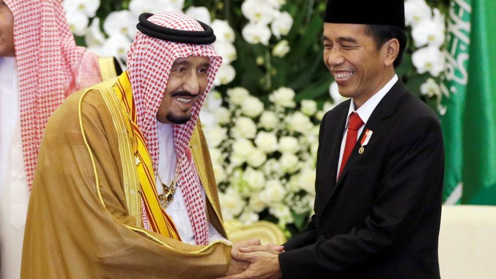 Saudi King Salman shakes hands with Indonesian President Joko Widodo.
