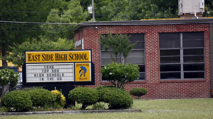 """A sign reading """"East Side High School: Top 500 High Schools in the U.S."""" sits outside a brick school building."""