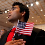 A man wearing a suit and tie holds an American flag at a naturalization ceremony.