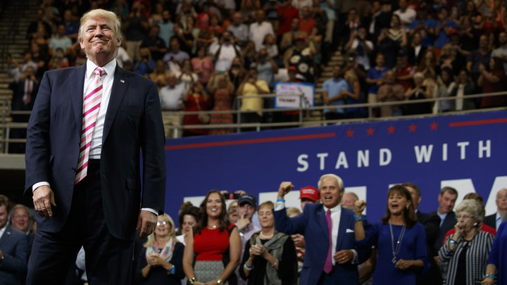 President Trump smiles at a campaign rally, with clapping supporters seen behind him.