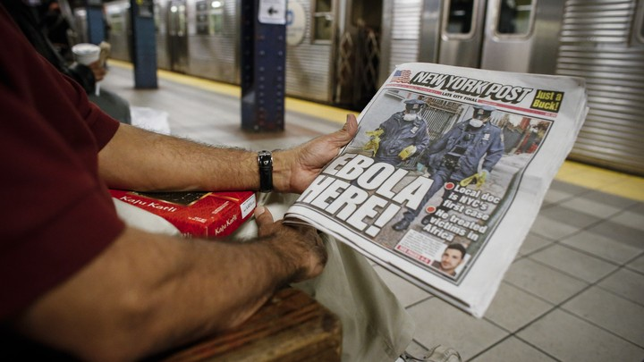 "A man holding a newspaper with ""Ebola here"" as the headline."
