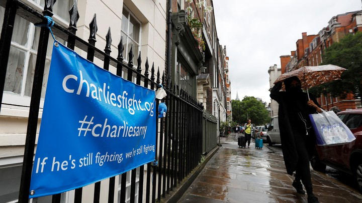 A woman walks past a banner left by supporters of Charlie Gard's family on July 27, 2017.