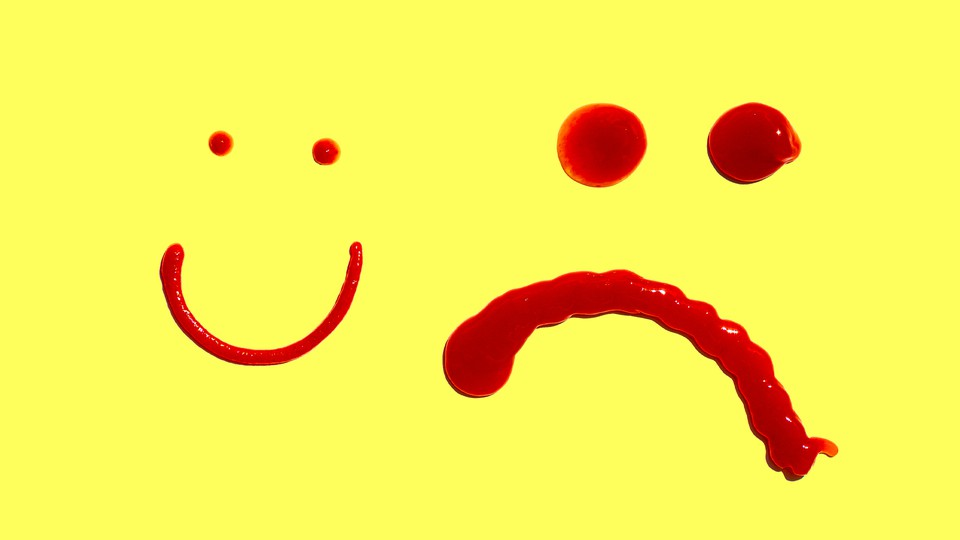 A smiley face and a frowning face made in ketchup, against a yellow background
