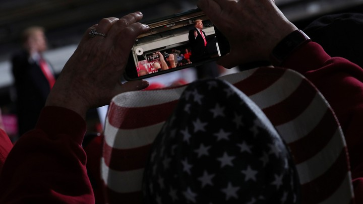 A voter in a hat patterned with an American flag films Donald Trump with a handheld phone.