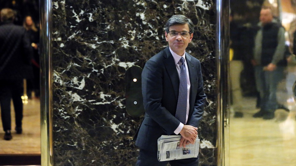 George Stephanopoulos stands in Trump tower and carries a newspaper.