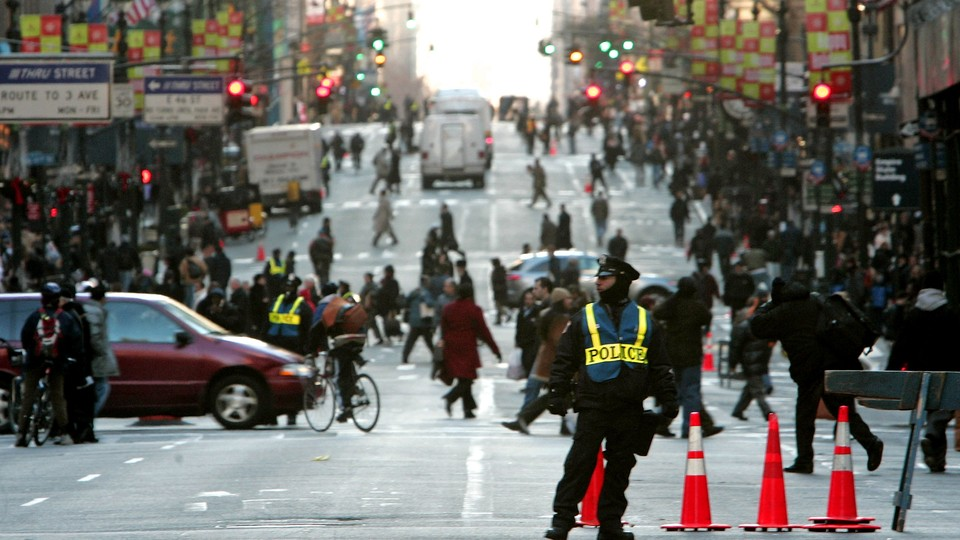 A police officer blocks traffic as pedestrians, bikers, cars, and trucks negotiate Fifth Avenue in New York.