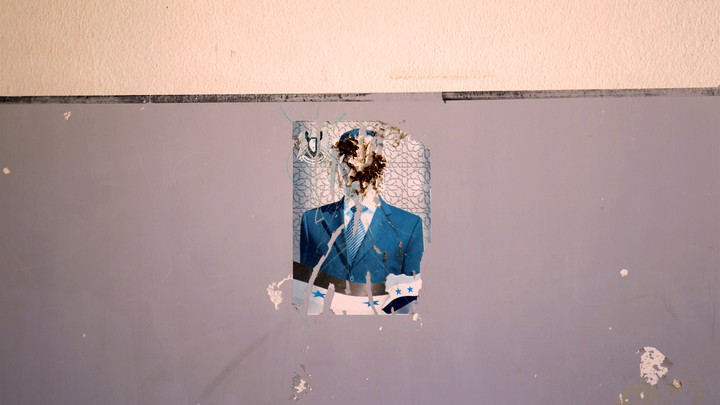 A defaced image of Syria's President Bashar al-Assad on a wall inside a school in Idlib province