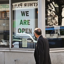 """A man walking past a storefront with a """"We are open sign."""""""