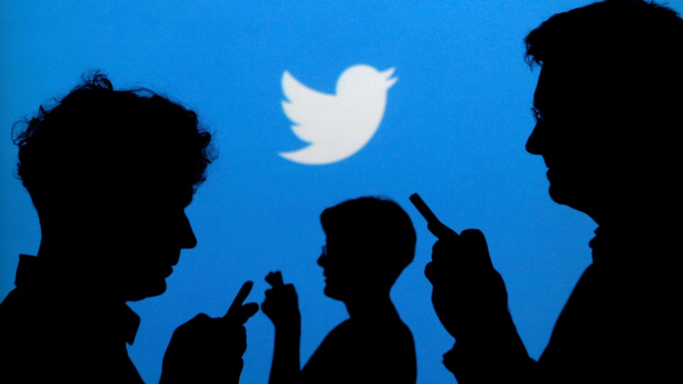 People in silhouettes look at their phones in front of a Twitter logo.