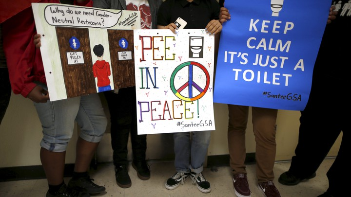 "Students hold signs including those reading ""pee in peace"" and ""keep calm it's just a toilet."""