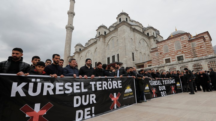 """People take part in a demonstration against the Christchurch attack following Friday prayers in Istanbul, Turkey. The banners read """"Say No to Global Terror!"""""""