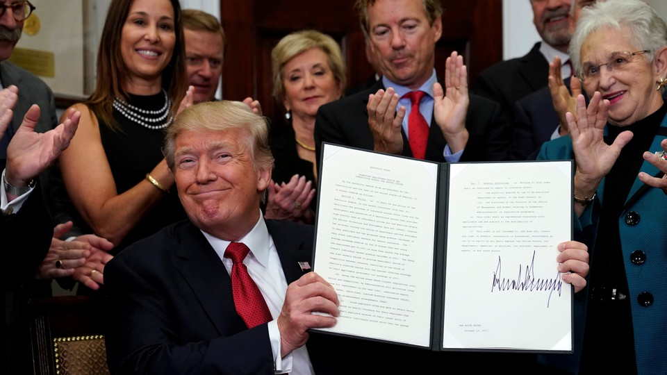 Donald Trump presents a signed executive order as an audience claps.