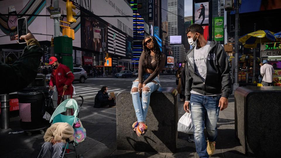 A man wearing a mask walking through Times Square