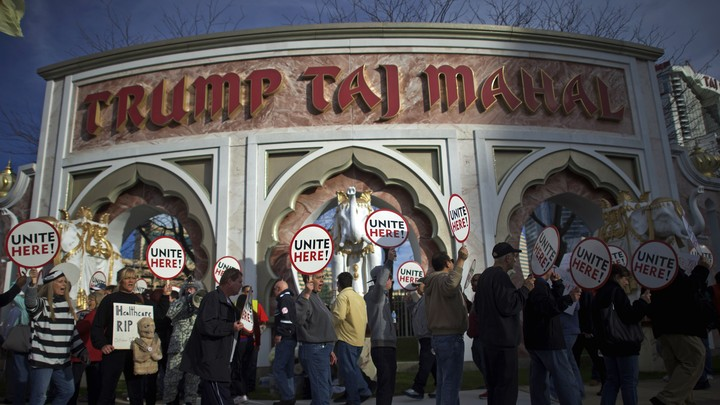 "People picket with signs that say ""Unite here"" in front of the Trump Taj Mahal casino."