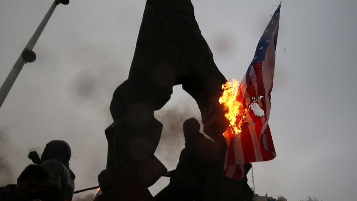 Iranians burn U.S. and Israeli flags.