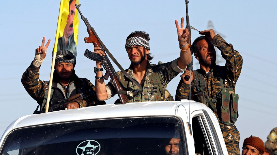 Three fighters of the Syrian Democratic Forces make the V-sign as their convoy passes
