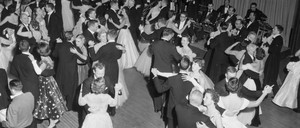 Couples in formal 1950s dress dance as a band plays.