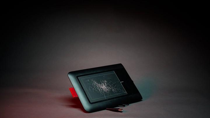 A photo illustration of a designer's cracked Wacom pen tablet