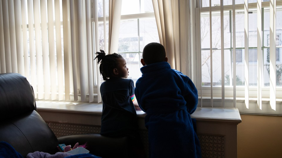 Two children look out a window