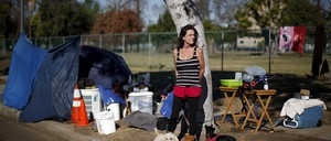 A homeless woman stands with her two dogs at her encampment.