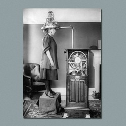 A black-and-white photograph of a woman with her head in a machine with exposed wires
