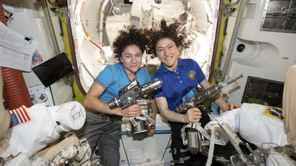 The astronauts Jessica Meir and Christina Koch pose with space drills before suiting up for their spacewalk.