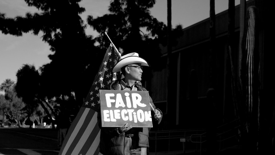 """A man holding an American flag and a sign that says """"Fair Election"""""""