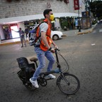 A volunteer wearing a dust mask rides a bike in the Roma neighborhood of Mexico City, Wednesday, September 20, 2017.