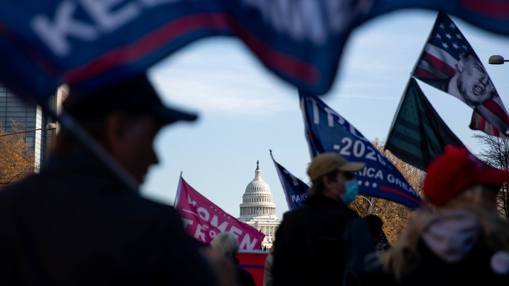 The U.S. Capitol is seen through a group of pro-Trump protesters waving flags on the streets of Washington, D.C.