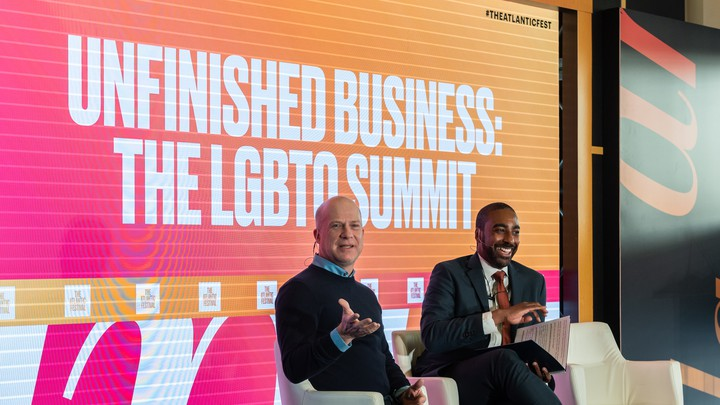 """Two men at The Atlantic Festival in front of a sign that reads """"Unfinished Business: The LGBTQ Summit."""""""