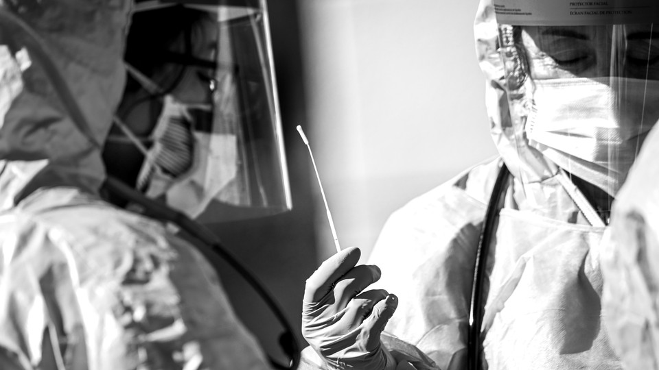 A black and white photo of two health care professionals in medical protective gear holding a cotton swab.