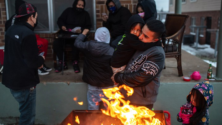 Texans stay warm by an open fire